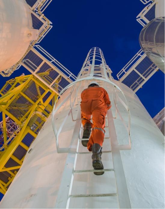 Voimalaitoksen työntekijä kiipeää tikkaita